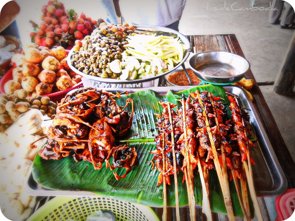street food in Cambodia - chicken and pork BBQ, preserved mangoes and fresh fruits.