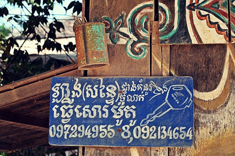 A locally-(hand)made sign. Signs like this are common in rural Cambodia. The can on top of the sign is an incense stick-holder.
